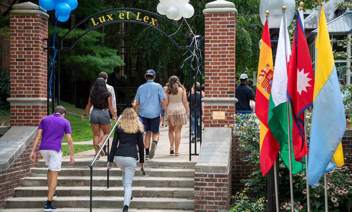 First-year students completing convocation in Fall 2020 by walking through the Lux et Lex arch.