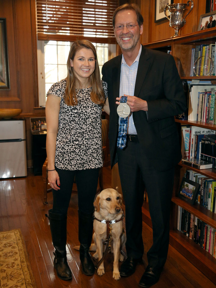 Meyers, with her guide dog, Birdie, presents F&M President Daniel R. Porterfield and the College with a special U.S. Olympic Committee medal last year.