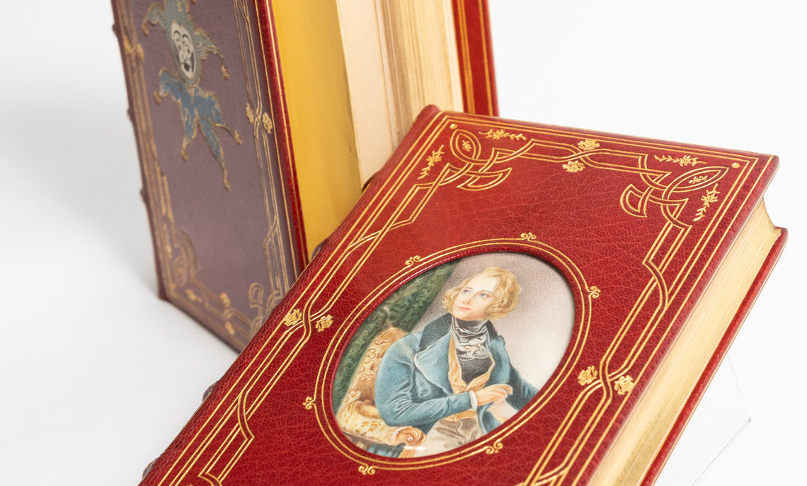"""Memoirs of Joseph Grimaldi,"" by Charles Dickens, is an example of Cosway-style binding. Books in this style have miniature paintings on the covers of richly tooled bindings."
