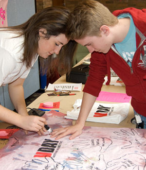 Morgan Shuster '10 traces the hand of Mike Weil '12 on a V-Day t-shirt.