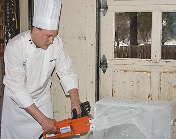 Wyatt Putt, executive chef of dining services, carves into a 300-pound block of ice.