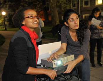 Tigist Hailu '11, left, and Dipti Balwani '11 adjust a projector in front of Distler House during Hailu's presentation on Monday evening. The project commemorated the 60th anniversary of the first African-American students to graduate from F&M.
