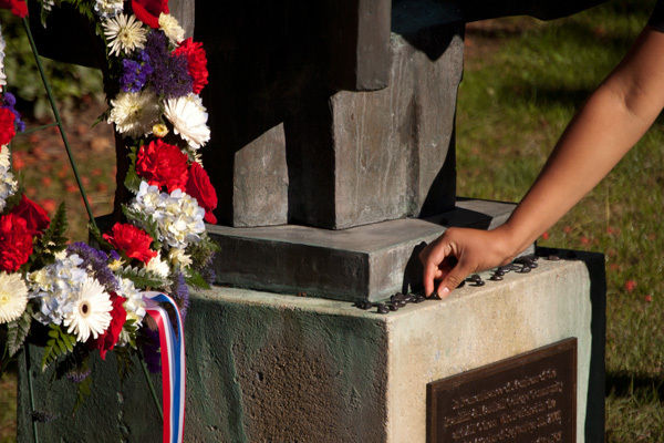 A member of the Franklin & Marshall community places a stone on the College's September 11 Memorial to help mark the 11th anniversary of the terrorist attacks. (Photo by Tim Brixius)