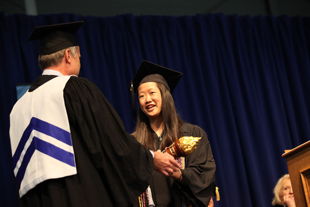 Amanda Loh '13, president of the Class of 2013, accepts the alumni torch from David Taylor '81. The passing of the torch marks the official acceptance of the class into the Franklin & Marshall Alumni Association. (Photo by Melissa Hess)