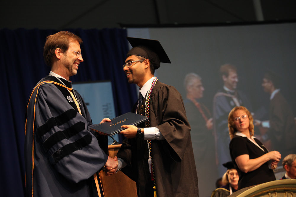 Akbar Hossain '13, recipient of numerous accolades for his academic and extracurricular achievements at F&M, receives his degree from President Daniel R. Porterfield (Photo by Melissa Hess).