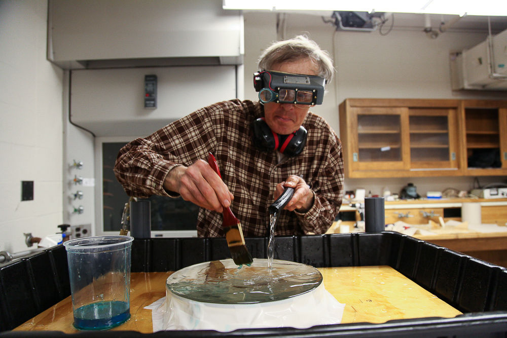 To clean the lens, John uses a simple homemade dish soap solution to rinse the glass while brushing the lens with a soft paintbrush. (Photo by Melissa Hess)