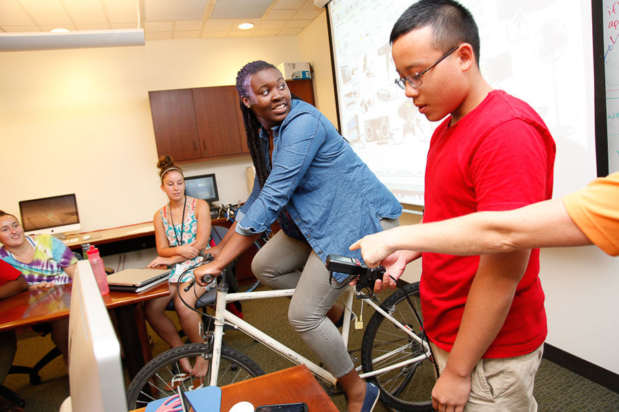 "F&M College Prep student Janai McGill pedals to generate energy during the second half of the ""Earth, Environment and Humanity"" class. Associate Dean of the College Suzanna Richter teaches students about conserving energy and resources. (Photo by Melissa Hess)"