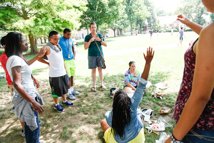 "During F&M College Prep's ""Earth, Environment and Humanity"" class, Sarah Dawson, director of F&M's Wohlsen Center for the Sustainable Environment, asks Janai McGill (hand raised), Sandra Osei-Frimpong, Vincent Do, Kevin Kelley, Madelyn Bowers (seated) to sort trash into piles of garbage, recyclables and compostables. (Photo by Melissa Hess)"
