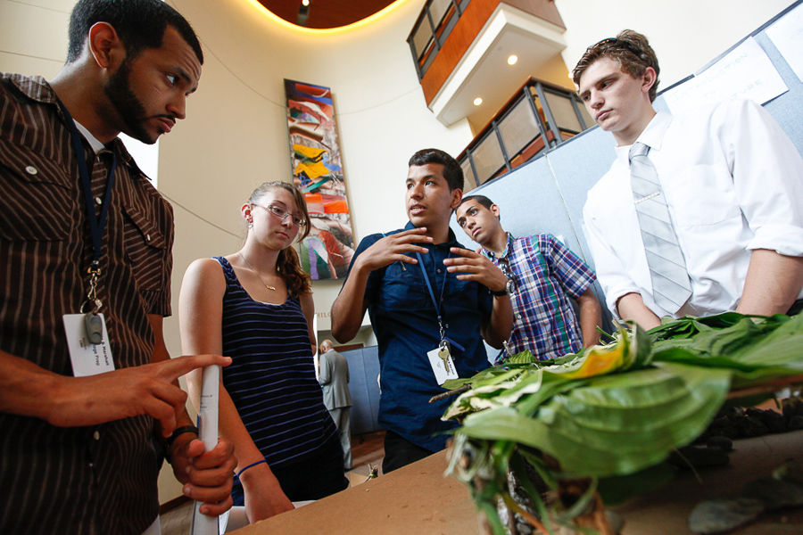 "F&M College Prep Facilitator Johnny Andrade (left) and students McKenna Brown, Gabriel Nunez and Tyler Reasner listen as ""Architectural Design"" student Pablo Ochoa explains the amphitheater model that was made with only natural materials to their peers during the project fair. (Photo by Melissa Hess)"