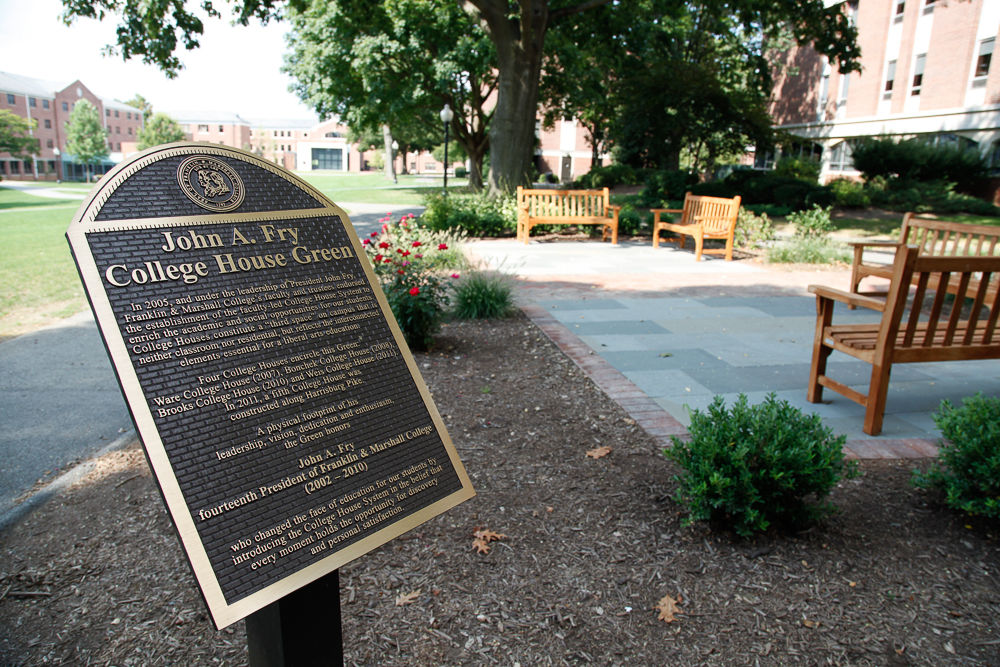 """Franklin & Marshall is recognizing the contributions of its 14th president with the """"John A. Fry College House Green,"""" a residential quadrangle bordered by the four original College Houses: Ware, Bonchek, Brooks and Weis. The final piece of the green was installed this summer: a bronze plaque and a garden with flagstones and bricks, benches and plants. (Photo by Melissa Hess)"""