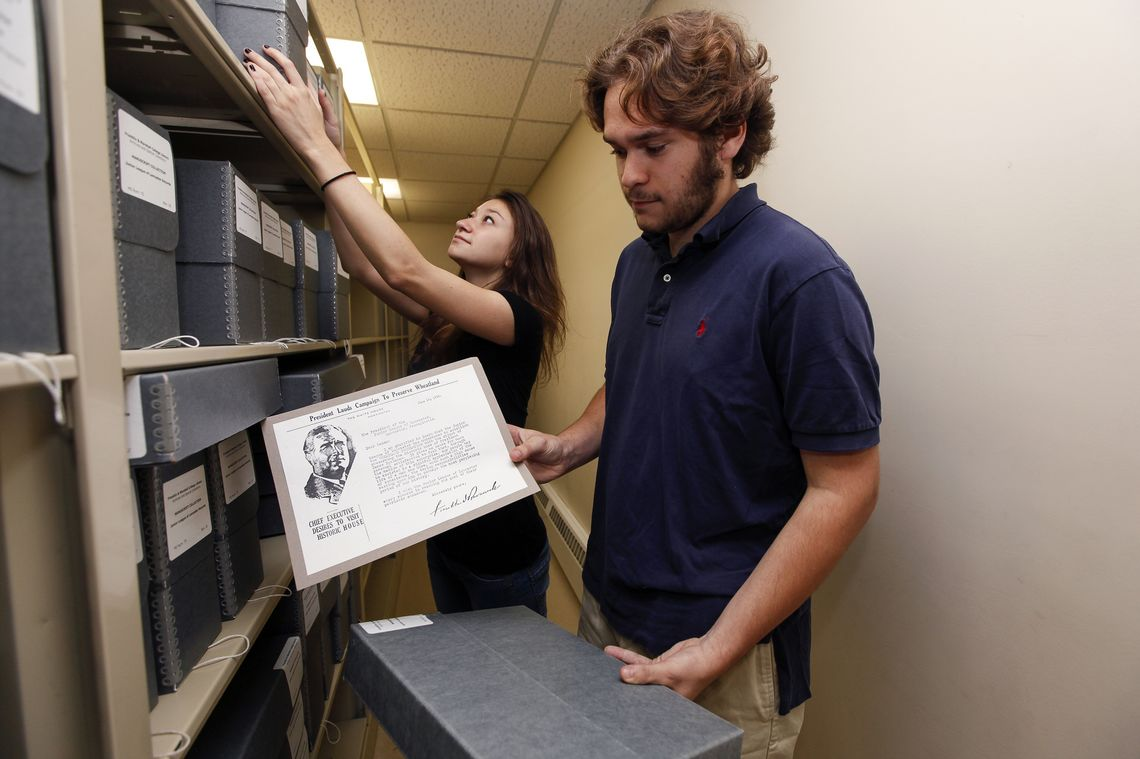 Franklin & Marshall students Krissy Montville and Rick Thoben spent the summer digitizing 90 years of the Junior League of Lancaster's records, and then storing the old records permanently in the F&M archives. Here, Thoben displays a letter from Franklin D. Roosevelt to the Junior League. (Photo by Melissa Hess)