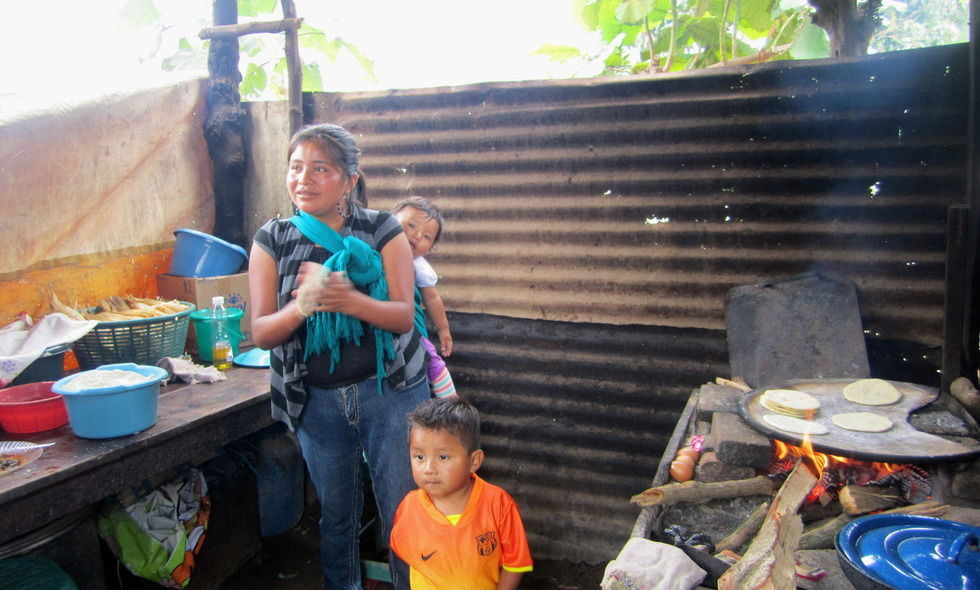 A woman with her children in Guatemala cooks over a wood-fire stove. Using solar stoves would minimize exposure to unhealthy gases and particulates that can accumulate when cooking with firewood indoors. (Photo courtesy of Anna Folz)