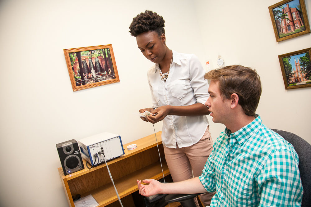 Since study volunteers are kept anonymous for privacy reasons, Franklin & Marshall College Hackman Scholars Markera Jones and Steele Schauer demonstrate how a volunteer is monitored to determine their emotion-regulation ability. (Photo by Melissa Hess)