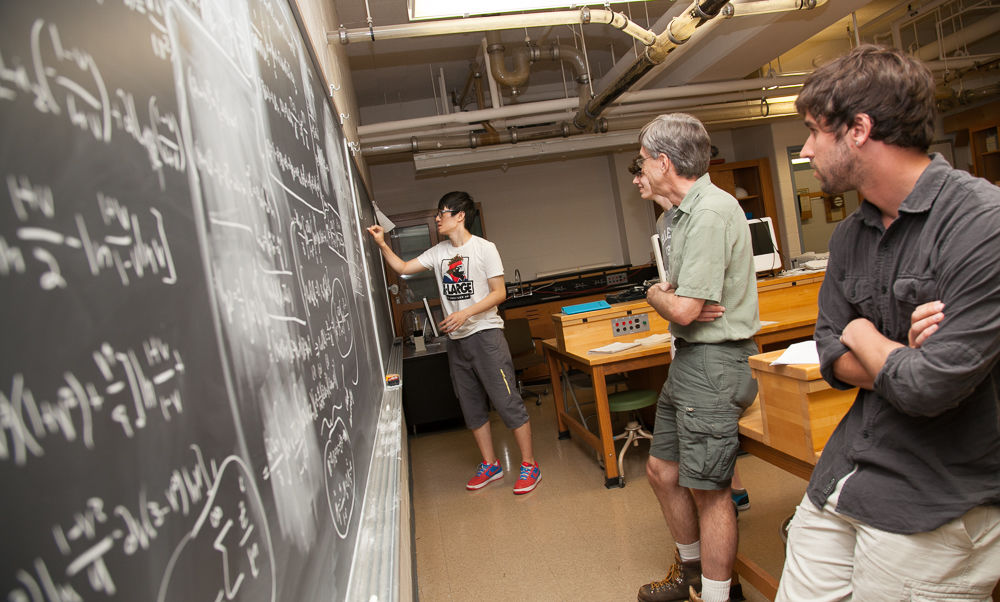 Franklin & Marshall College Physics Professor Greg Adkins, with funding from the National Science Foundation, has embarked this summer on a three-year project to study the properties of an exotic atom called positronium. His research assitants are three Hackman Scholars, from right: senior Matthew Salinger, and juniors Christian Parsons (center, next to Adkins) and Ruihan Wang. (Photo by Melissa Hess)