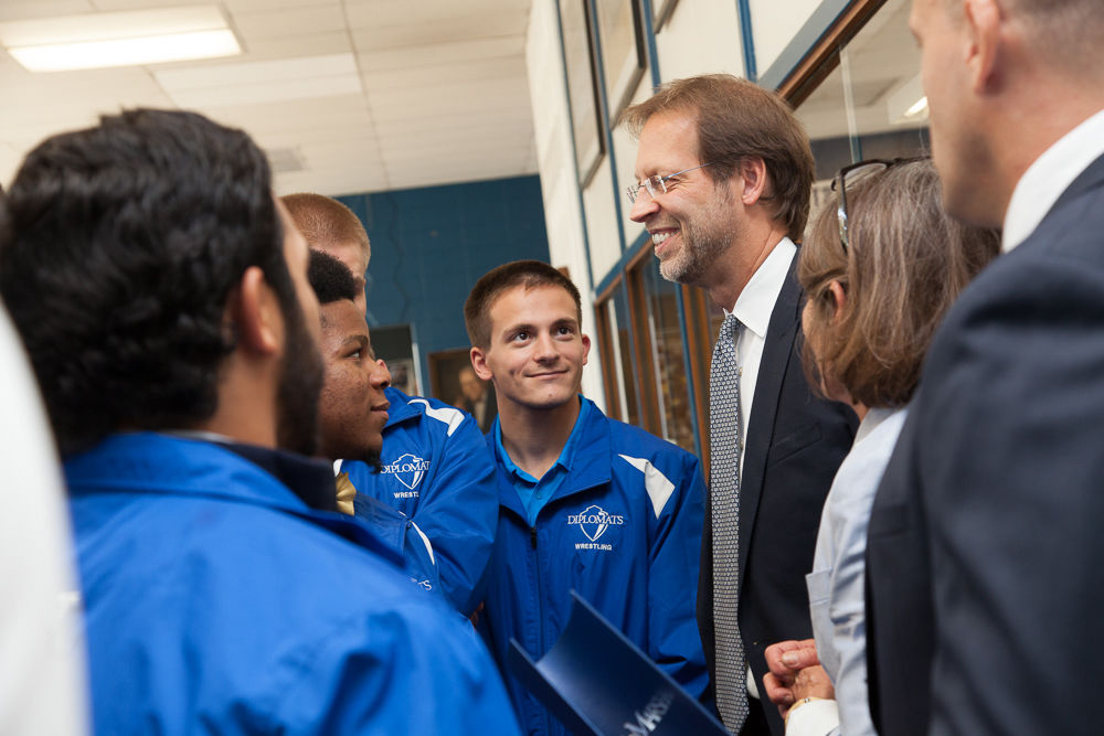 President Daniel R. Porterfield talks with members of the wrestling team following Franklin & Marshall College's announcement Sept. 15 that a $5 million gift from prominent geologist David Lehman, a 1968 alumnus, will endow F&M's NCAA Division I wrestling program for generations of student-athletes to come. (Photo by Melissa Hess)